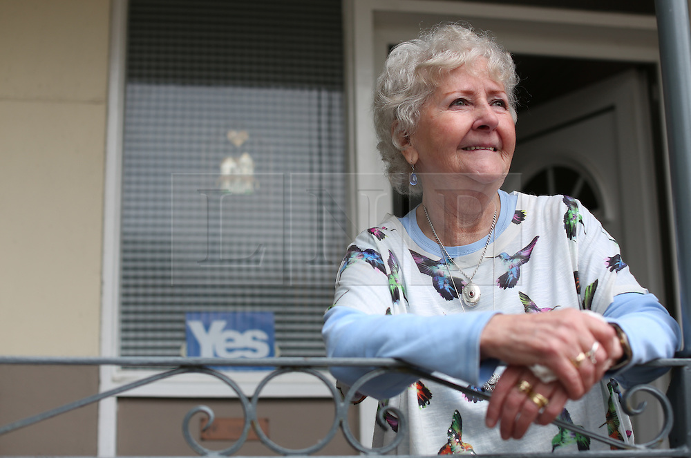 © Licensed to London News Pictures. 14/09/2014. Edinburgh, UK. Ms Ise Duncen, of Dumbiedykes Road, shows a Yes vote sign outside her front door. With only  four days left to decide on the Scottish referendum, the latest polls give a mixed picture of opinions. Photo credit: Isabel Infantes / LNP