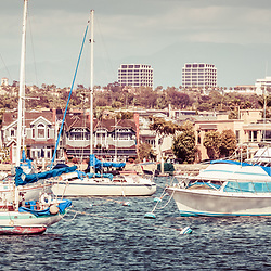 Newport Beach skyline retro panorama photo. Panoramic picture ratio is 1:3 and Includes boats in Newport Harbor (Newport Bay) with Newport Beach Fashion Island office buildings in the background. Photo has a vintage 1960s tone.
