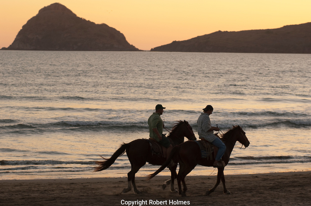 Riding horses on the beach at sunset, Mazatlan, Mexico