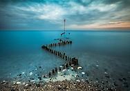 Groynes at sea at Heacham Beach, Norfolk, during the sunrise.