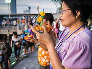 "17 NOVEMBER 2013 - BANGKOK, THAILAND: A woman prays before floating her krathong in the Chao Phraya River near Wat Yannawa in Bangkok. Loy Krathong (also written as Loi Krathong) is celebrated annually throughout Thailand and certain parts of Laos and Burma (in Shan State). The name could be translated ""Floating Crown"" or ""Floating Decoration"" and comes from the tradition of making buoyant decorations which are then floated on a river. Loi Krathong takes place on the evening of the full moon of the 12th month in the traditional and they do this all evening on the 12th month Thai lunar calendar. In the western calendar this usually falls in November. The candle venerates the Buddha with light, while the krathong's floating symbolizes letting go of all one's hatred, anger, and defilements       PHOTO BY JACK KURTZ"