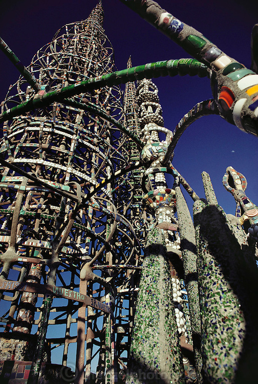 Watts Towers in Los Angeles, California. Designed by Simon Rodia 1921-1955. Untrained as an architect, engineer, or builder, Simon Rodia created a complex of towers that rose over one hundred feet tall. Composed of structural steel rods and circular hoops connected by spokes, the towers incorporate a sparkling mosaic of found materials including pottery, seashells, and glass. Rodia's house, destroyed by fire in 1957, resided within the complex..  Declared hazardous by the city of Los Angeles, the towers were threatened with demolition until an engineer's stress test proved them structurally sound. They have since been designated a cultural monument.