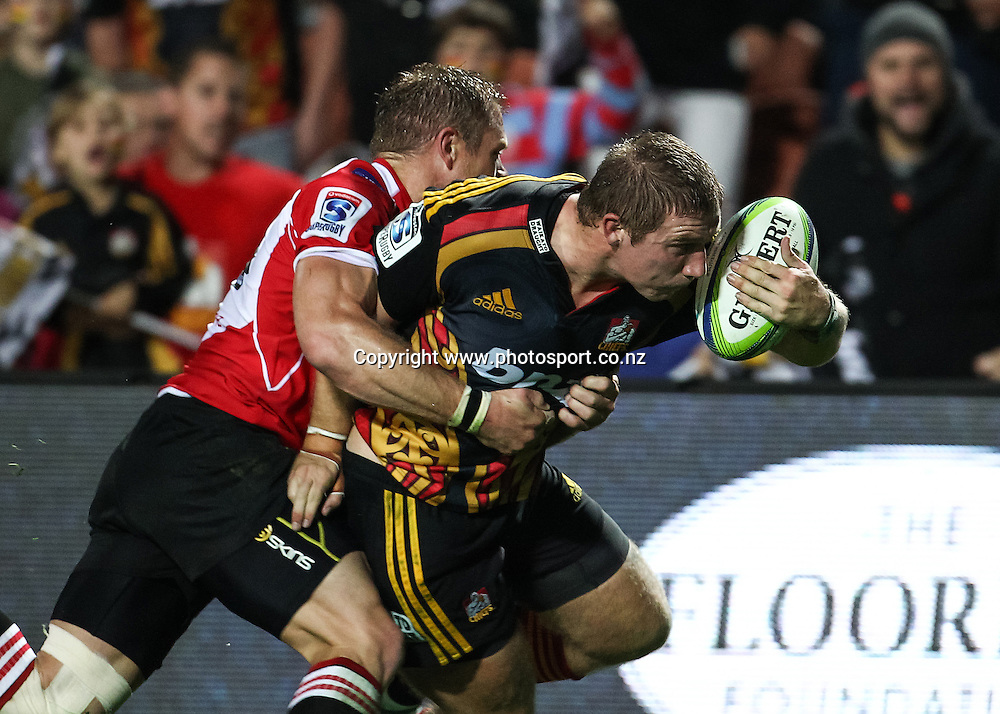 Lions' Deon van Rensburg attempts to tackle Chiefs' Nathan Harris during the Super 15 Rugby union match - Chiefs v Lions at Waikato Stadium, Hamilton, New Zealand on Saturday 3 May 2014.  Photo:  Bruce Lim / www.photosport.co.nz