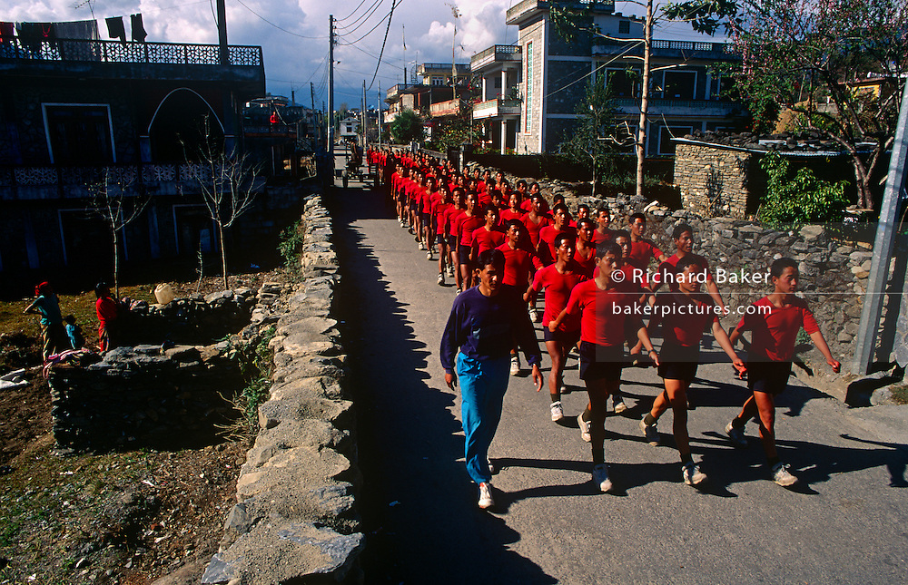 Young Nepali boys in army red march though a Pokhara street after being recruited for the Gurkha Regiment in the Btitish army. This recruitment test for the Gurkha Regiment is part of a tough endurance series to find physically perfect specimens for British army infantry training. For example they will need to perform 25 straight-kneed sit-ups at a 45° slant both within 60 seconds to pass. 60,000 boys aged between 17-22 (or 25 for those educated enough to become clerks or communications specialists) report to designated recruiting stations in the hills each November, most living from altitudes ranging from 4,000-12,000 feet. After initial selection, 7,000 are accepted for further tests from which 700 are sent down here to Pokhara in the shadow of the Himalayas. Only 160 of the best boys succeed in the journey to the UK. The Gurkhas have been supplying youth for the British army since the Indian Mutiny of 1857.