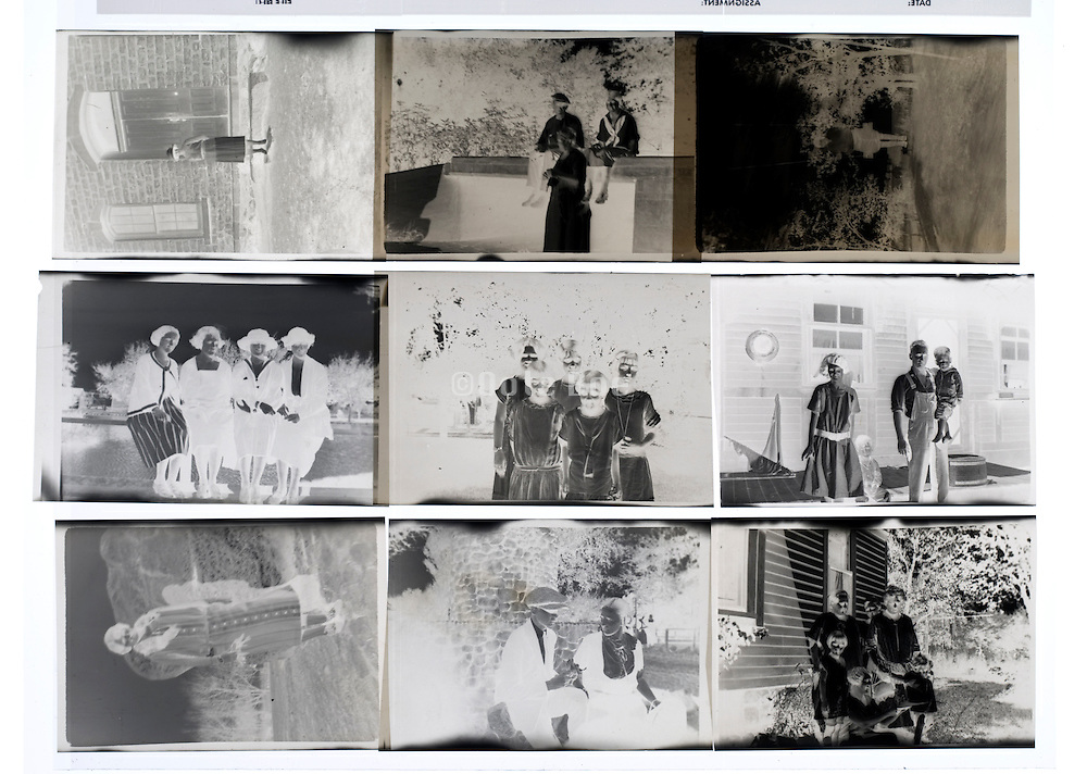negatives of old photos with groups of people posing