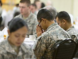 SPC. Travis Singeo bows his head in prayer at a Thanksgiving dinner for soldiers of JBLM held in Chris Knutzen hall of the Anderson University center on Wednesday, Nov. 26, 2014. (Photo/John Froschauer)