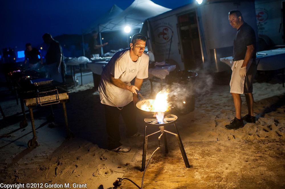 Sagaponack, NY - 6/29/12 - Joe Liehr, an employee of the caterer Hamptons Clambakes, sears tuna during a clambake at Sagg Main Beach in Sagaponack, NY June 29, 2012.     (Photo by Gordon M. Grant)