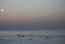 surfers in the ocean during a full moon