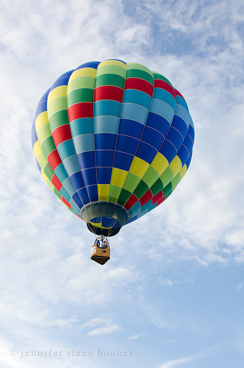 The rainbow-colored 'Tracer' floats through white clouds in a blue sky, Crown of Maine Balloon Fair, Presque Isle, Maine.