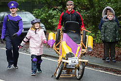Windlesham, UK. 26 December, 2019. Competitors take part in the annual fancy dress Windlesham Boxing Day Pram Race charity event along a 3.5-mile course through Windlesham village with stops at local pubs along the route.