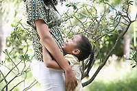 Girl (5-6 years) hugging mother standing in garden side view