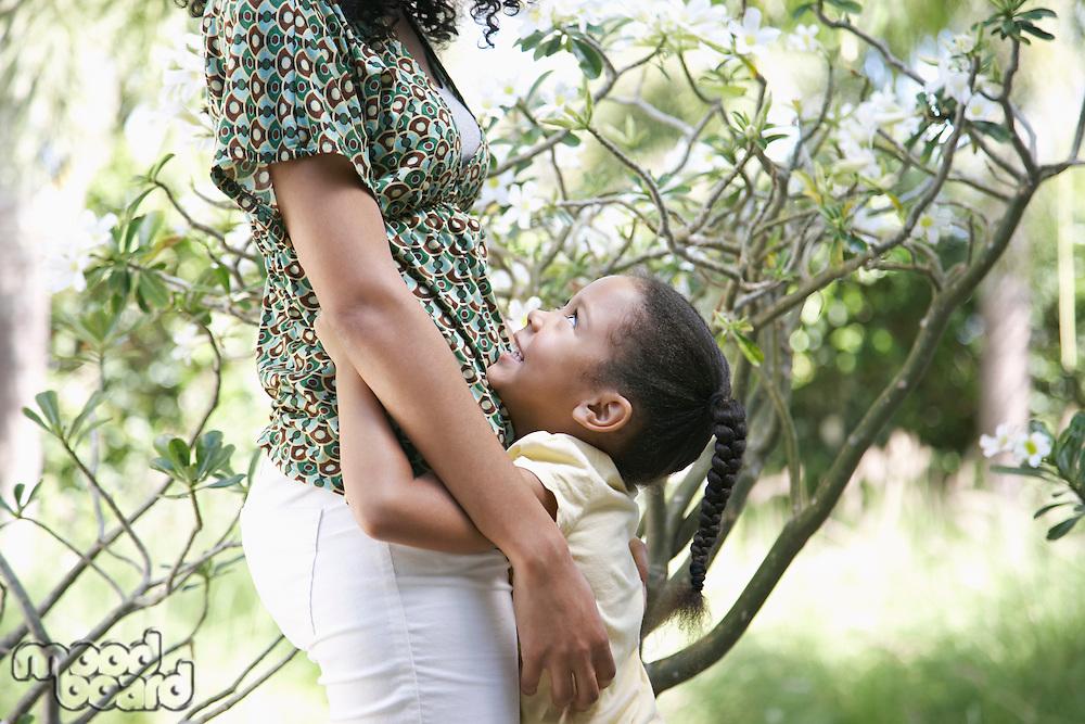 Girl (5-6 years) hugging mother standing in garden side view