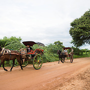 BAGAN, Myanmar (Burma) - A couple of horse-drawn buggies go down a dirt road in Bagan, Myanmar. The buggies are a popular tourist activity in the region.
