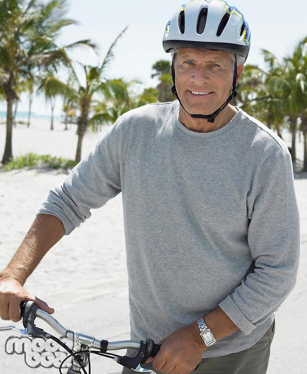 Senior man on bicycle on tropical beach