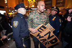 © licensed to London News Pictures. New York City, New York, USA. 3/01/12. Iraq veteran Sgt Shamar Thomas (US Marines) takes part in protest. Arrests take place during protests in Grand Central Station take place in Manhattan against the recently passed National Defence Authorisation Act (NDAA), which protesters are concerned introduced indefinite detention powers to be used against those suspected of terrorism. Photo credit: Jules Mattsson/LNP