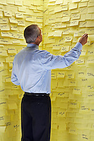 Middle-aged man standing in front of wall covered in sticky notes reading