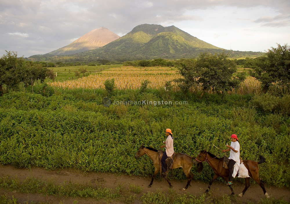 "Two men ride horses along a trail with part of the San Cristobal volcanic complex in the background, Chinandega Nicaragua. Nicaragua is often referred to as the ""Land of Lakes and Volcanoes."" The area is rich with wildlife, flora and fauna, and there are large areas of preserved land."