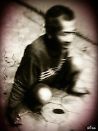 Blurry top view of Vietnamese man crouched on a sidewalk in Hanoi, Vietnam, Southeast Asia