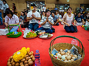 31 MAY 2017 - CHACHOENGSAO, THAILAND: People with hard boiled eggs used for offerings at Wat Sothon (also spelled Sothorn) in Chachoengsao, Thailand. The temple is one of the largest and most visited in Thailand. People make merit by paying to wrap the Buddha statues in orange robes. The temple is most famous because people leave hard boiled eggs as an offering at the temple. They ask for business success or children and leave hundreds of hard boiled eggs.      PHOTO BY JACK KURTZ