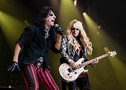 © Licensed to London News Pictures. 28/10/2012. London, UK.   Alice Cooper (left) and his guitarist Orianthi Panagaris (right) performing live at Wembley Arena for Alice Cooper's Halloween Night of Fear.  Alice Cooper (born Vincent Damon Furnier; February 4, 1948) is an American rock singer, songwriter and musician whose career spans more than four decades. With a stage show that features guillotines, electric chairs, fake blood, boa constrictors, and baby dolls, Cooper has drawn equally from horror movies, vaudeville and garage rock to pioneer a grandly theatrical and violent brand of heavy metal designed to shock. Photo credit : Richard Isaac/LNP
