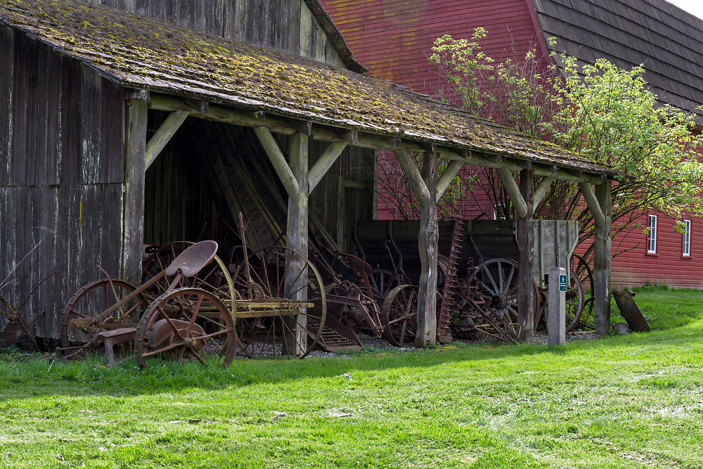 Old farm equipment in a storage area on the side of the Gable Roof Barn (1898) at the Annand Rowlatt Farmstead.  This farmland was first used by Joseph and Sarah Anne Annand and later by Len Rowlatt until his death in 1972.  The property is now part of Campbell Valley Regional Park in Langley, British Columbia, Canada.