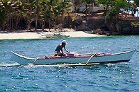 Man on a fishing boat in the clear waters of Boracay Island, Philippines.