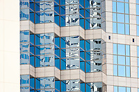 Windows in a downtown Seattle high-rise office building reflect the blue sky and the building structure takes on a zig-zag appearance from the angle of view.