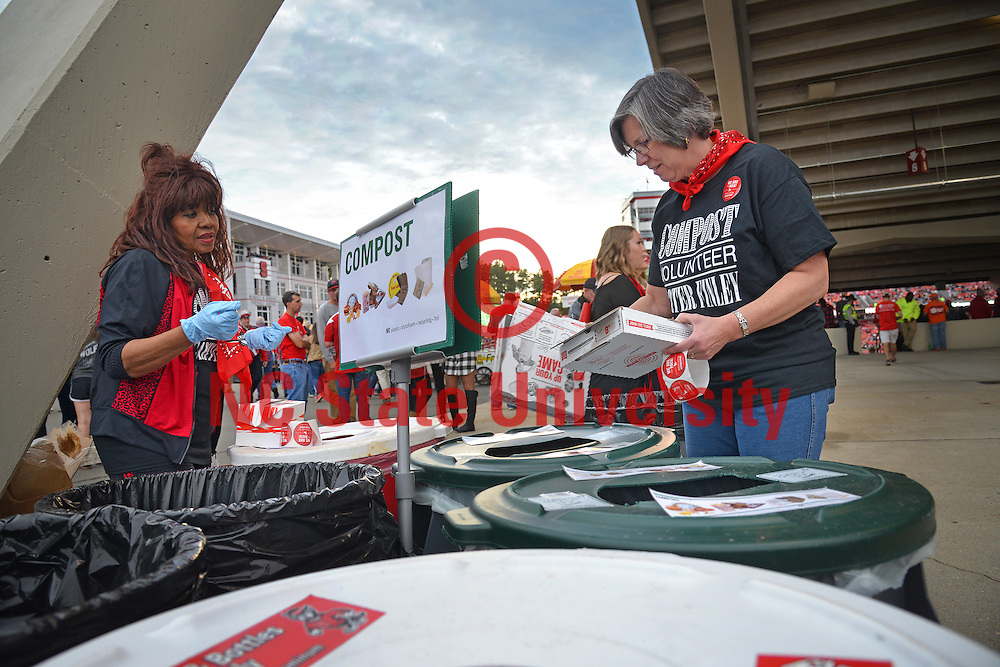 NC State University compost volunteer Lynn Odom (right) puts pizza boxes in the proper composting bins during halftime of the Wolfpack football game against Clemson University in Raleigh, NC. NC State photo by Roger Winstead