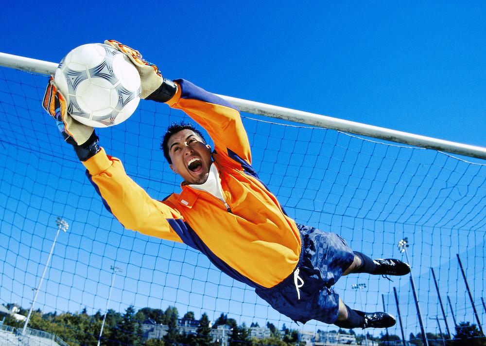 Soccer Goalie dives to stop a shot on goal