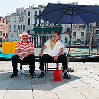 Two gondoliers rest in the shade of a large umbrella on the day the Italian Government and Heath Ministry has issued several warning for the current heath wave