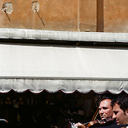 A young boy watches musicians play in front of a cafe near Piazza San Marco. Venice, Italy. 1st May 2011. Photo Tim Clayton