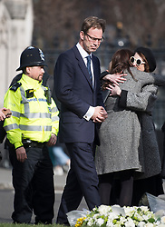© Licensed to London News Pictures. 22/03/2018. London, UK. TOBIAS ELLWOOD MP looks at flowers left on Parliament Square, outside the Houses of Parliament in Westminster, London on the one year anniversary of the the Westminster Bridge Terror attack. A lone terrorist killed 5 people and injured several more, in an attack using a car and a knife. The attacker, 52-year-old Briton Khalid Masood, managed to gain entry to the grounds of the Houses of Parliament and killed police officer Keith Palmer. Photo credit: Ben Cawthra/LNP