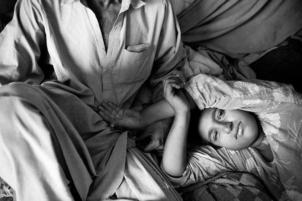 Hamida takes a rest placing her hand in her husbands lap. Karachi, Pakistan, 2010