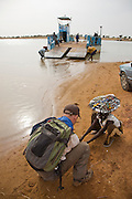 Djenné, Mali, 2009 - Traveler negotiates with a child for a peice of jewelry while a small cargo ferry prepares to load passengers and vehicles. Sandbars along the bank of the Niger River have prevented the ferry from getting closer to shore.