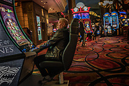 Man playing a version of slots.  Las Vegas, Nevada.