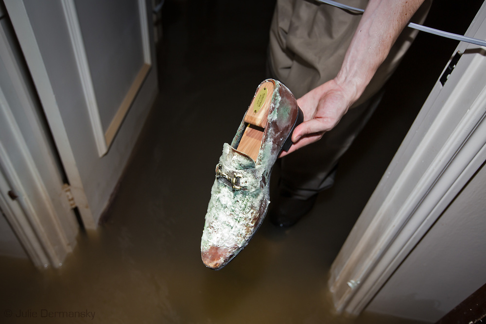 Days after Hurricane Harvey first made landfall in Texas, a man holds up a shoe in his home in the Woodlands ll subdivision off Gessner  Road and Bayou Shadows, in Houston, Texas that is covered in mold.  The flooding in this part of Houton was impacted by Harvey's rainstomr and  water released from the  Addicks Dam.  When the Addicks Reservoir started to over flow the U.S. Army Corps of Engineers began releasing water from the Addicks Dam, which had already started to overflow.