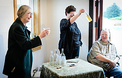 Carol Tuynman of Haines (left) toasts Phyllis Sage (center) and Joanne Waterman during an open house for Sage&rsquo;s and Waterman's restoration of the fire hall located on the historic Fort William H. Seward grounds in Haines, Alaska.<br /> <br /> The fire hall was restored over a two-year period by owners Sage and Waterman who also own the fort&rsquo;s original guardhouse, now a bed and breakfast, located next door to the fire hall.<br /> <br /> After being absent from the historic Fort Seward skyline since approximately the 1930s, the 60-foot tower of the fort&rsquo;s fire hall has been restored to its original height. The building and tower, built around 1904 in Haines, Alaska, was shortened to approximately half its height in the 1930s for unknown reasons. The restoration included rebuilding a missing 35-foot section of the 60-foot tower whose purpose was to dry fire hoses. The tower restoration was completed by building its four sections on the ground and then hoisting those sections with a crane into place on top of each other.<br /> <br /> Through the years, the historic Fort Seward area, a former U.S. Army post, has been referred to as Fort William H. Seward, Chilkoot Barracks, and Port Chilkoot. The National Historic Landmarks listing record for the fort says that &quot;Fort Seward was the last of 11 military posts established in Alaska during the territory's gold rushes between 1897 and 1904. Founded for the purpose of preserving law and order among the gold seekers, the fort also provided a U.S. military presence in Alaska during boundary disputes with Canada. The only active military post in Alaska between 1925 and 1940, the fort was closed at the end of World War II.&rdquo; <br /> <br /> The bottom portion of the fire hall is being leased as commercial space. Due to fire code restrictions there is no public access to the upper portion of the tower.