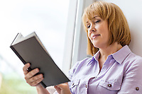 Mature woman reading book by window at home