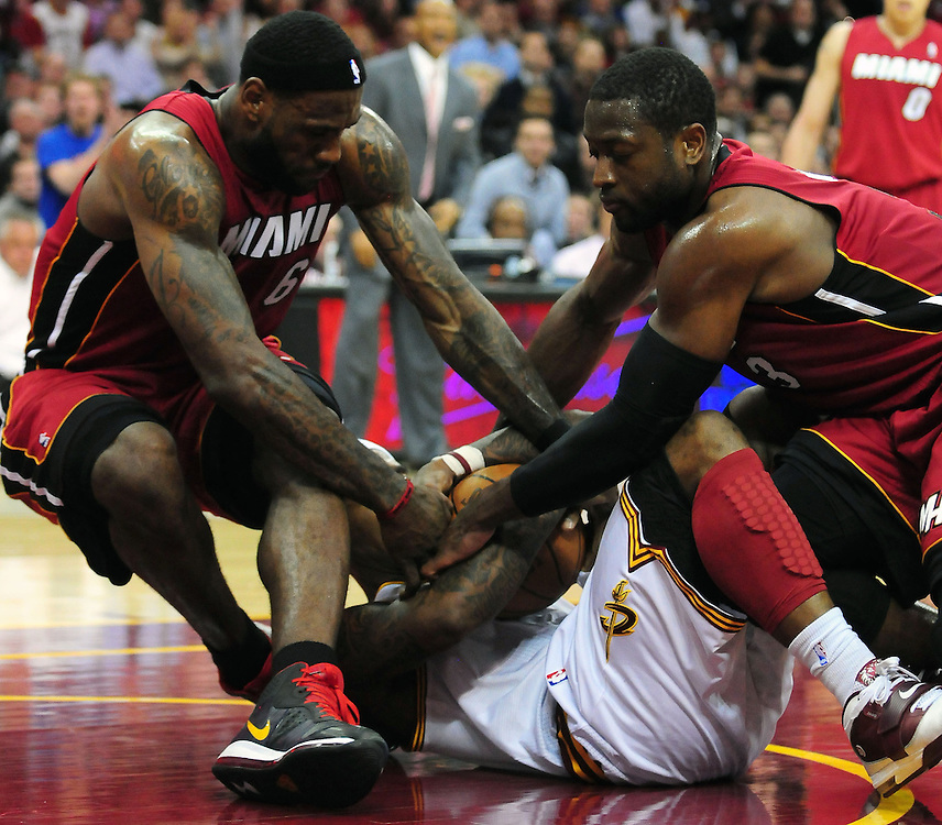 March 29, 2010; Cleveland, OH, USA; Miami Heat small forward LeBron James (6) and shooting guard Dwyane Wade (3) fight for a loose ball with Cleveland Cavaliers point guard Daniel Gibson (1) during the fourth quarter at Quicken Loans Arena. The Cavaliers beat the Heat 102-90. Mandatory Credit: Jason Miller-US PRESSWIRE