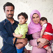 Bashir 29 holding his daughter Zaahra 2 ½ years old and his wife  Shefqe 24 years old holding her 7 months old girl Hamid from Chardere district of Afghanistan in Moria camp, Lesvos, Greece