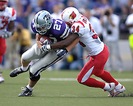 Kansas State wide receiver Jordy Nelson (27) is wrapped up by Louisville defensive back Bobby Buchanan (34) after picking up a first down in the second half, at Bill Snyder Family Stadium in Manhattan, Kansas, September 23, 2006.  The 8th ranked Louisville Cardinals beat K-State 24-6.