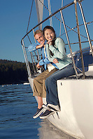 Young couple sitting on side of sailboat (portrait)