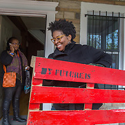 WASHINGTON, DC - NOV 16 :  Kimberly Gaines, a community organizer, carries a pallet November 16, 2013, from fellow community organizer Sheshat Walker's porch to her truck for a community harvest festival (which was postponed due to weather) at the Riverside center in Deanwood, Washington, DC. The pallets will be put up around the park for people to write their feelings on. Gaines and Walker are working on a project called My Deanwood, where they photograph community members and write stories about them. (Photo by Evelyn Hockstein/For The Washington Post)