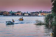 Båtar på Riddarfjärden i skymning med Rosenbad och Riksdagshuset i bakgrunden i Stockholm. Fotograferad från Söder Mälarstrand.