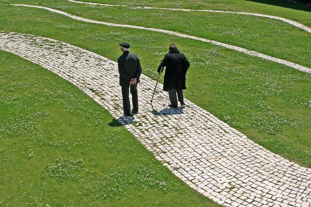 Una pareja de ancianos pasea por un parque de Oporto (Portugal)