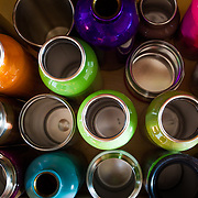 A drawer full of stainless water bottles highlights an environmental cause of not purchasing bottled water from the grocery store.