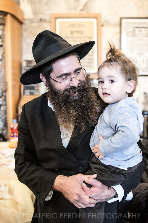 An Haredi (ultra-orthodox) Jewish settler with a young girl at a family gathering in Hebron.