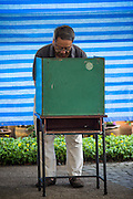 03 MARCH 2013 - BANGKOK, THAILAND: . A man marks ballot to the ballot box in a polling place in Benchasiri Park in Bangkok. Bangkok residents went to the polls Sunday to elect a new governor. Voter turnout was expected to be heavy for a local election. Pongsapat Pongchareon, the Pheu Thai candidate is thought to hold a slight lead over Sukhumbhand Paribatra, the Democrats' candidate. There are a total of 25 candidates in the election but only Pheu Thai and the Democrats are given a chance of winning.    PHOTO BY JACK KURTZ