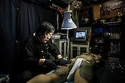 Tokyo, March 2013- Tattoo master Horitoshi performing a body suit tattoo at his atelier in the Ikebukurao area. Body suit tattoos are usually associated with members of the Yakuza, Japan's mafia.