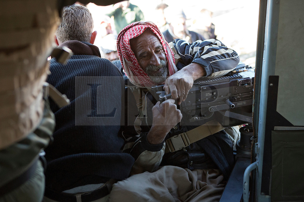 &copy; Licensed to London News Pictures. 11/12/2014. Sinjar Mountains, Iraq. An elderly Yazidi refugee hangs from an M240 machine gun as he attempts to climb in to an Iraqi Air Force Mi-17 helicopter, that will evacuate both he and his family from Mount Sinjar.<br /> <br /> Although a well publicised exodus of Yazidi refugees took place from Mount Sinjar in August 2014 many still remain on top of the 75 km long ridge-line, with estimates varying from 2000-8000 people, after a corridor kept open by Syrian-Kurdish YPG fighters collapsed during an Islamic State offensive. The mountain is now surrounded on all sides with winter closing in, the only chance of escape or supply being by Iraqi Air Force helicopters. Photo credit: Matt Cetti-Roberts/LNP